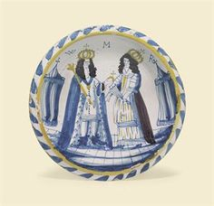 A LONDON DELFT PORTRAIT CHARGER OF WILLIAM AND MARY  CIRCA 1690  Painted with the crowned Sovereigns in coronation robes, he holding a sceptre and orb, she a fan, beneath the initials WMR and flanked by two tall tents on a paved ground, within an ochre line and blue-dash rim, on a circular foot  12 5/8 in. (32.1 cm.) diameter