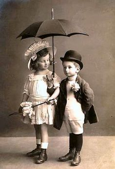 Boy and girl under an umbrella. vintage photo
