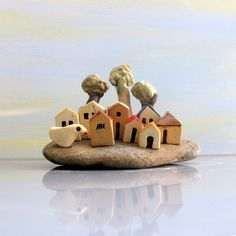 This is a ceramics and pottery handmade sculpture.  This ceramic sculpture includes 8 white clay miniature houses as a lovely miniature neighborhood.  It