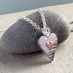 A gorgeous silver heart necklace with smaller copper heart. Hand cut from sterling silver and softly hammered.
