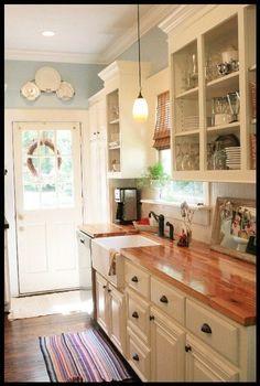 white cabinets, butcher block countertops, farmhouse sink and pretty blue walls by tulasi.fanelli