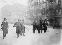 A line of armed revolutionaries of the Spartacist movement stand in a Berlin street during the German Revolution of 1918 - 1919.