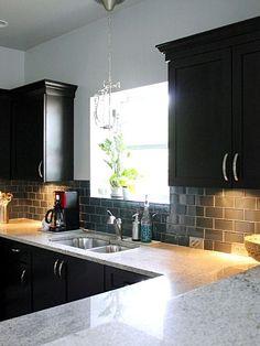 Black cabinets and a glass backsplash provide a modern and updated look. Backsplash With Dark Cabinets, Black Kitchen Cabinets, Black Kitchens, Kitchen Redo, Kitchen Backsplash, New Kitchen, Cool Kitchens, Kitchen Remodel, White Cabinets