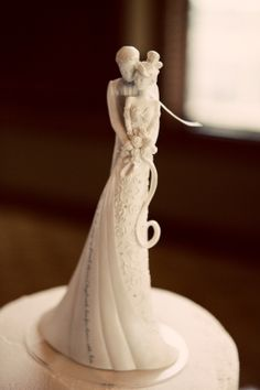 """Language Of Love Cake Topper    9"""" Gina Freehill wedding cake topper made of a resin and stone mix. Topper is embellished with rhinestones and a fabric tulle veil. Love quote on bride's dress reads, """"This day I will marry my friend, the one I laugh with, live for, dream with, love."""""""