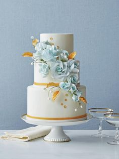 Classic round cake tiers are the perfect canvas for pale blue roses, Grecian gold leaves and petite circles, giving this wedding confection a timeless feel with a hint of whimsy.