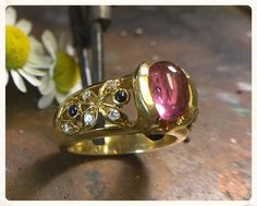 Pink tourmaline estate ring:  This unique estate ring showcases a lovely pink tourmaline cabochon in a partial bezel setting.  The gemstone is flanked by diamonds and sapphires in a pierced floral design. Two small sapphire cabochons are bezel-set in the head. Finger size is 6.75.