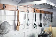 "Hooks above the stove hold everything needed to put together a meal. ""A lot of farmhouse-style kitchens do not have upper cabinets they just have lower cabinets, so what you will find is floating shelves and storage,"" says Brian."