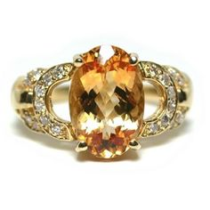 The center of this ring is graced with a beautiful peach/gold color 3.55 carat, oval cut, Topaz, accented with 0.25 carats of round brilliant cut diamonds set throughout the mounting. The ring is made of 18 karat yellow gold and weighs 4.1 pennyweight.