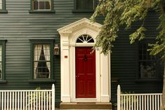 love the red door in contrast with the white trim and dark house.