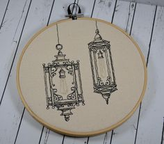 "Victorian Lanterns design, machine embroidered on natural canvas. It is framed in an 8"" wooden hoop and has a ribbon to hang it on the wall. The back is neatly finished with cream felt to cover the st"
