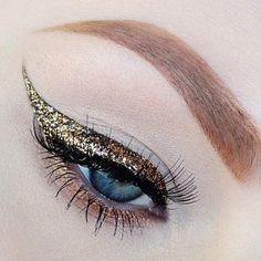 Gold winged glitter eye makeup. Beautiful.