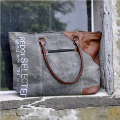 <p>This Zipped Shoulder Bag features a charcoal grey colored tarp with drop leather handles and leather accents.