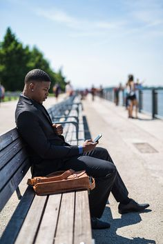 Businessman sitting on bench looking at cell phone