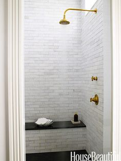 Brass fittings, white subway tile, black bench seat and flooring