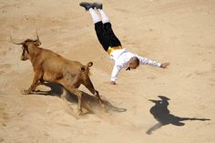"""A """"recortador"""" leaps over a wild bull during an exhibition of riding and acrobatic skills at the bullring on the third day of the annual San Fermin festival in Pamplona, Spain"""