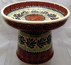"""$55.00-$67.29 This is a raised Polish pottery wet/fresh/canned food dish for cats and smaller dogs.  This wet food dish measures 5 and 1/8"""" high to the rim, has a 6"""" diameter/1"""" deep bowl and holds 1 and 1/2 cups of food. The wide shallow bowl will not irritate sensitive whiskers and the food is easily accessible to the pet. This dish is especially beneficial to flat faced cats and smaller flat m ..."""