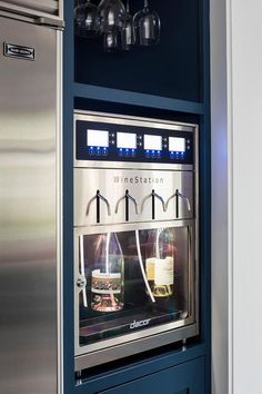 A SubZero refrigerator is located beside a Dacor Wine Station fixed beneath a wine glass rack mounted to the top of a blue shelf painted in Benjamin Moore Van Deusen Blue.