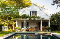 This home just oozes charm...from the teak furniture, potted boxwoods, pergola, swimming pool and all that lush greenery.