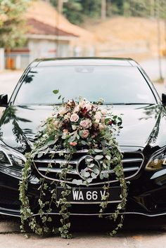 A sleek and shiny black wedding car with a sprawling light pink and dark maroon floral arrangement on the bonnet // Luke and Jasmine reached out to Natasha of Peak Xperience to plan their rich, marsala-hued wedding. The couple wed in an all-white ceremony on the lawn of Tanarimba, Janda Baik, and celebrated their Malaysia wedding with a rustic, autumn barn-inspired reception, as these photos by Peter Herman Photography show. #rusticweddingphotography