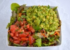 Loaded Guaco Garbanzo Salad 1 clove of garlic 4 T. red onion, divided 1 handful of cilantro, divided juice of ½ lemon ½ tsp. salt 2 avocados 1 can garbanzo beans, rinsed and drained ¼ c. finely minced celery (about 2 stalks) Mixed baby greens 1 cucumber, chopped 1 ½ c. grated carrots (3-4 carrots) 2 chopped tomatoes 1-2 T. balsamic vinegar