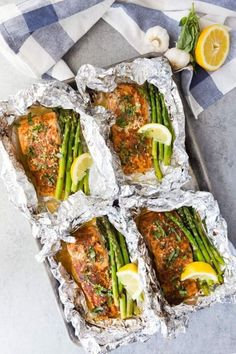Four salmon fillets on a baking tray in foil with asparagus and lemon wedges with garlic and lemon in the background Baked Salmon And Asparagus, Lemon Garlic Salmon, Baked Salmon Recipes, Asparagus Recipe, Seafood Recipes, Dinner Recipes, Fresh Asparagus, Tilapia, Foil Packet Meals