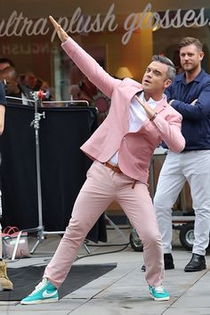 yes, that's robbie williams. but apart for the pink suit—isn't that a Benefit Store in the background?