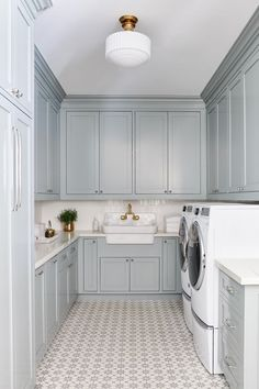 Gray u-shaped laundry room is clad in Cement Tile Shop Atlas Tiles lit by a vint. Gray u-shaped laundry room is clad in Cement Tile Shop Atlas Tiles lit by a vintage white glass sem Blue Laundry Rooms, Mudroom Laundry Room, Laundry Room Layouts, Laundry Room Remodel, Laundry Room Cabinets, Blue Cabinets, Laundry Room Design, Mud Rooms, Laundry Room Floors
