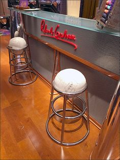 A handwritten Robert Graham® scrawled across perforated metal provides a visual centerpiece and branding for the service counter. Unique Wembley stools provide the seating, and look plump and comfo...