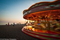 Dusk falls on the beach at Brighton in East Sussex. Couples enjoy the  warm summer evening as children ride on a carrousel / merry-go-round.