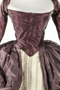 A mauve/gray changeable silk rove a la polonaise late 1770s with boned, low pointed black panels, internal skirt loops, the sleeves applied with 1770s double tiered embroidered muslin engageants. Posted on Kerry Laylor Auctions. The petticoat they say is a 1770s panel of mauve and green striped silk.