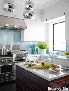 In the kitchen of a Manhattan apartment designed by Amanda Nisbet, Tom Dixon Mirror Ball pendants pr... - Tara Donne