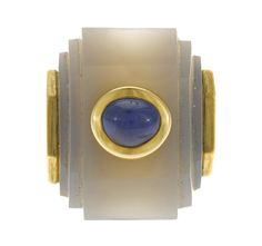A chalcedony and sapphire ring  composed of an oval-shaped sapphire cabochon, measuring approximately: 8.5 x 7.0mm, set in a carved chalcedony, measuring approximately: 27.2 x 21.9mm; mounted in eighteen karat gold