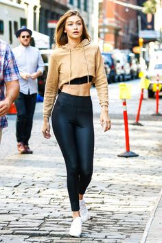 Gigi Hadid in black leggings, nude cropped hoodie and white sneakers.