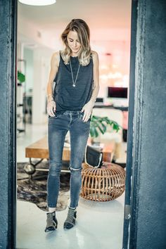 dark grey ripped knees skinny jeans, dark grey sleeveless shirt with low armpits, and a long necklace.