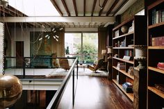 In+its+previous+incarnation,+the+exposed+mezzanine+was+a+no+man's+land+used+for+storage.+Scott+and+Jo+added+their+client's+Seventies+chairs+and+lined+the+walls+with+bookshelves