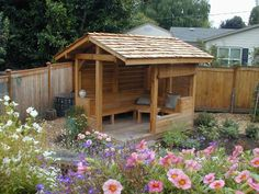 A very small garden structure provides a year round retreat from the sun or rain in this urban backyard built from sustainably harvested wood. Structure & Garden Installation by Apogee Landscapes.