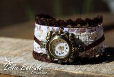 Montre romantique chocolat. Montre fantaisie en bronze montée sur un tissu fleuri brun sur fond blanc. Bordée de velours marron et surmontée d'un ruban chocolat. Fermoir boucle et chaînette couleur bronze.