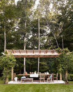Bobby Flay's Hamptons House - Bobby Flay Home With Stephanie March - In the outdoor dining area, teak chairs by Restoration Hardware surround a custom-made teak dining table under a pergola of wisteria-wrapped cedar.