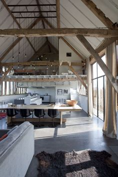 Wooden beams, concrete floor, large window, hanging lightbulbs