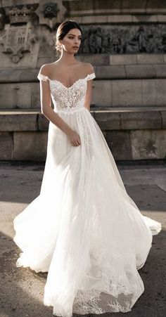 This long lace off the shoulder beach wedding gown is stunning! I love the almost corset fitted look with the long flare!