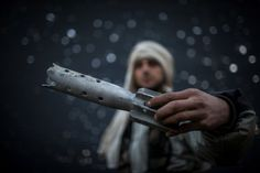 A Free Syrian Army fighter displays a damaged ordinance in Aleppo