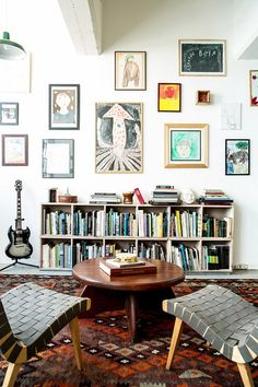 Colorful living room with gallery wall, book shelves and a large area rug