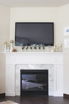 white fireplace with marble subway tile