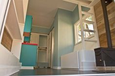 A small built in bench seat is flanked by a ladder that's been incorporated into the design.   #TinyHouseforUs