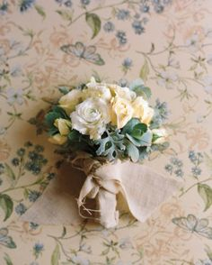"""bouquet of ranunculus, roses, dusty miller, and succulents, wrapped in linen.  See the """"Bouquets"""" in our  gallery"""