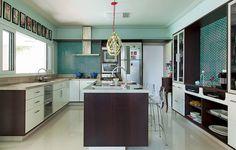 Azulejos retrô revestem as paredes da cozinha projetada pela arquiteta Andrea Murao. No espaço amplo, a ilha central fica em evidência. Ali, fica uma das pias. Serve também para as refeições