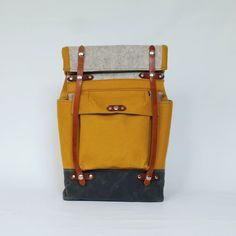 Color: Ochre Yellow, Light Gray, Faded Blue, with Honey-Brown Leather Materials: Felted Wool Exterior, Waxed Canvas Base, Waterproof Harness Leather,