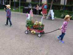 Kid pulls a Radio Flyer during Floral Wagon Parade. The fun family event was part of Balboa Park's big Garden Party!