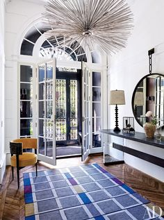 In a Boston townhouse, the entrance hall features a standout chandelier, which hangs above a Samuel colorful rug.