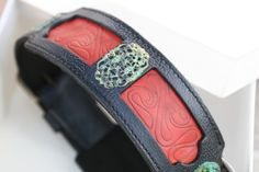"Samartha Black and Red Leather Dog Collar was inspired by the art of Ancient China. Samartha means ""plentiful wealth"". It is a perfect choice for large breed females such as Fila Brasileiro, Cane Corso, Tosa and Dogo Canario but other breeds can easily wear it too.  The overlying black leather is firm and decorated with verdigris brass patina filigree stampings. The underlying red leather is with curvilinear embossing.  Samartha black and red leather dog collar is hand stitched and machine…"